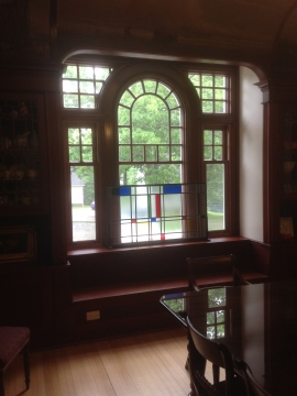 Assembly of stained wooden architectural windows and asymeric sashes hung windows